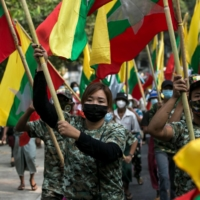 Military supporters carry Myanmar's national flags during a protest in Yangon on Saturday to demand an investigation of the Union Election Commission. | AFP-JIJI