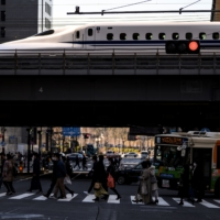People cross a street while a bullet train arrives in Tokyo on Sunday. | AFP-JIJI