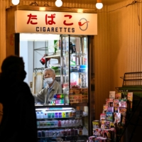 A masked cigarette vendor sits in his shop in Tokyo on Monday. | AFP-JIJI