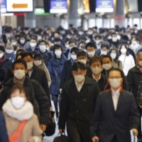 Mask-wearing commuters walk through Shinagawa Station in Tokyo on Tuesday. | KYODO