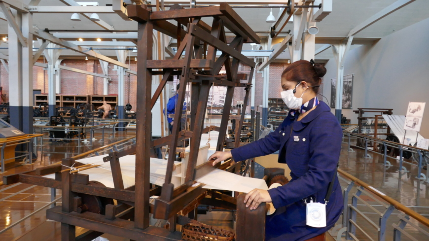 A staff member demonstrates the technology behind one of the earliest looms. | JANE KITAGAWA