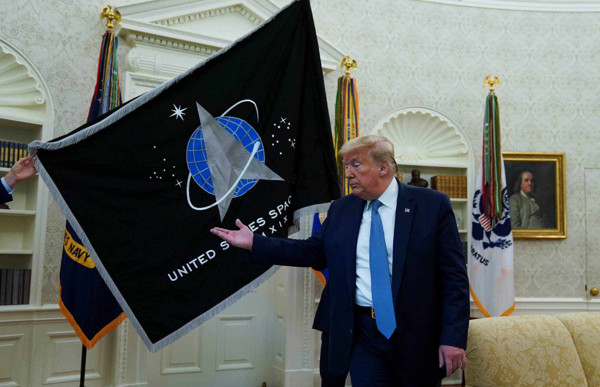 Former U.S. President Donald Trump inspects the U.S. Space Force flag during a presentation of the banner in the Oval Office in Washington in May.    REUTERS