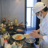 Custom cuisine: Reki Uchiyama, a chef who was dispatched to a customer's home to prepare meals, cooks in the kitchen at the residence in Tokyo's Shinagawa Ward.  | KYODO