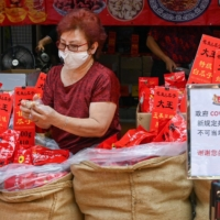 A vendor sells nuts from a shop next to a sign telling the public to prevent the spread of the coronavirus, in Chinatown, Singapore, on Jan. 5. | AFP-JIJI
