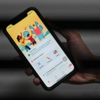 Singapore's contact-tracing app, TraceTogether, is displayed on a smartphone. Nearly 80% of residents are said to have signed up to use the app. | AFP-JIJI