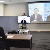 Industry minister Hiroshi Kajiyama (on screen, left) meets online with Takahama Mayor Yutaka Nose (front and on screen, right) in the town of Takahama, Fukui Prefecture, on Friday. | KYODO