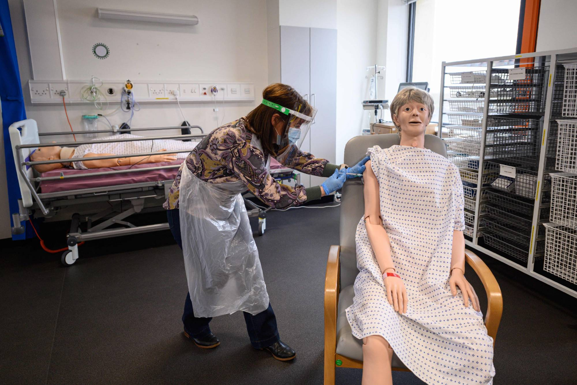 A volunteer practices administering an intramuscular injection with a training model during training to prepare volunteers to be deployed to assist in Britain's COVID-19 vaccination program, in the Allam Medical Building at the University of Hull on Saturday.   AFP-JIJI