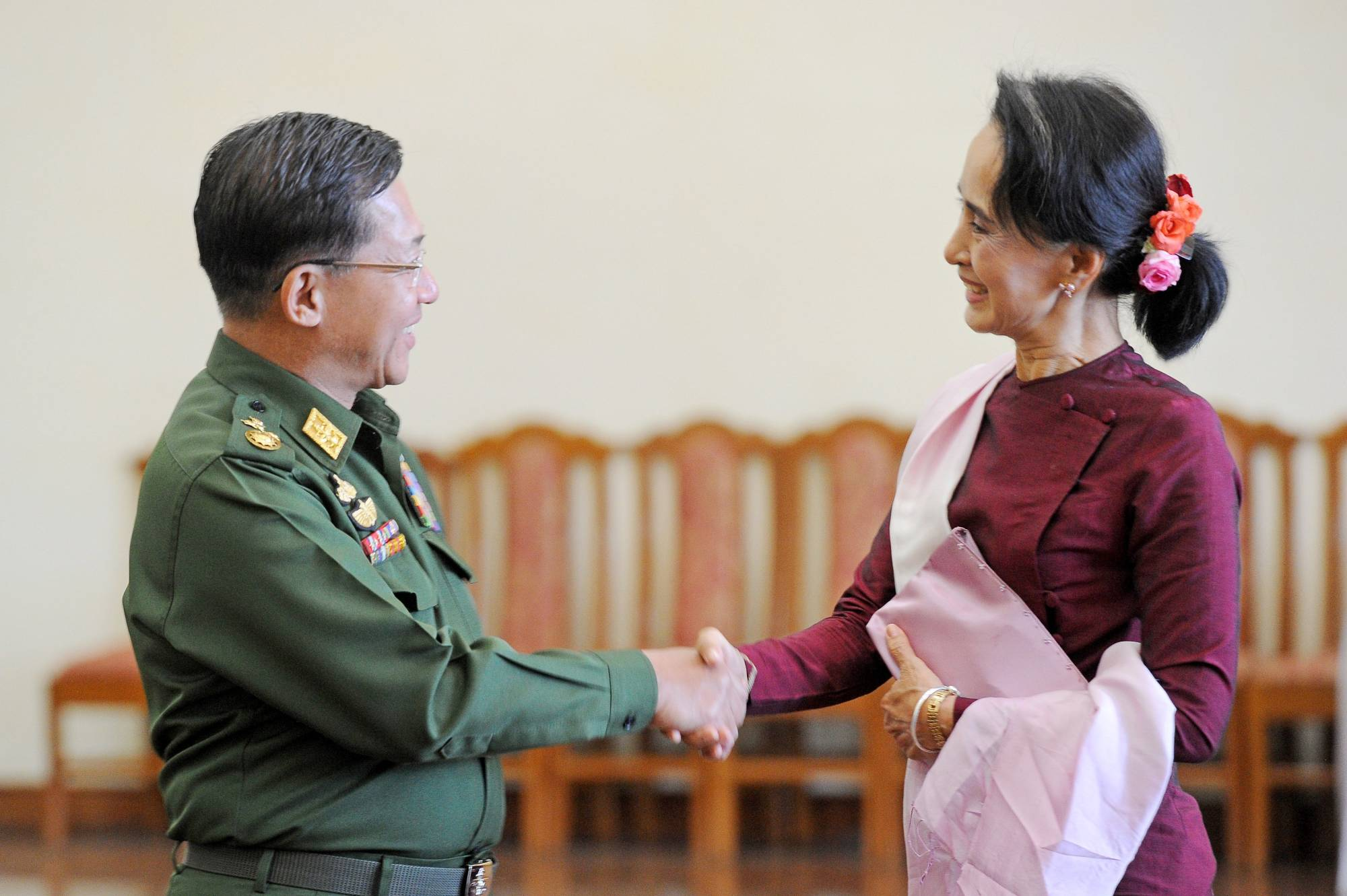 Myanmar military chief Gen. Min Aung Hlaing and National League for Democracy party leader Aung San Suu Kyi shake hands after their meeting at the commander in-chief's office in Naypyidaw, Myanmar, in December 2015. | AFP-JIJI