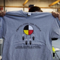 A person holds up a T-shirt that was given out to those who received a COVID-19 vaccine at Menominee Indian High School. | REUTERS