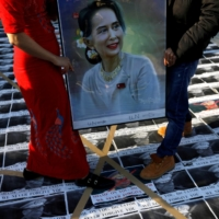 Myanmar protesters residing in Japan stand on pictures of army chief Min Aung Hlaing as they rally against the coup, including the arrest of the country's de facto leader, Aung San Suu Kyi, at United Nations University in Tokyo on Monday. | REUTERS