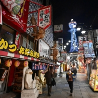 Few pedestrians can be seen on a nearly empty street in the Shinsekai shopping and amusement district of Osaka on Jan. 12. | KYODO