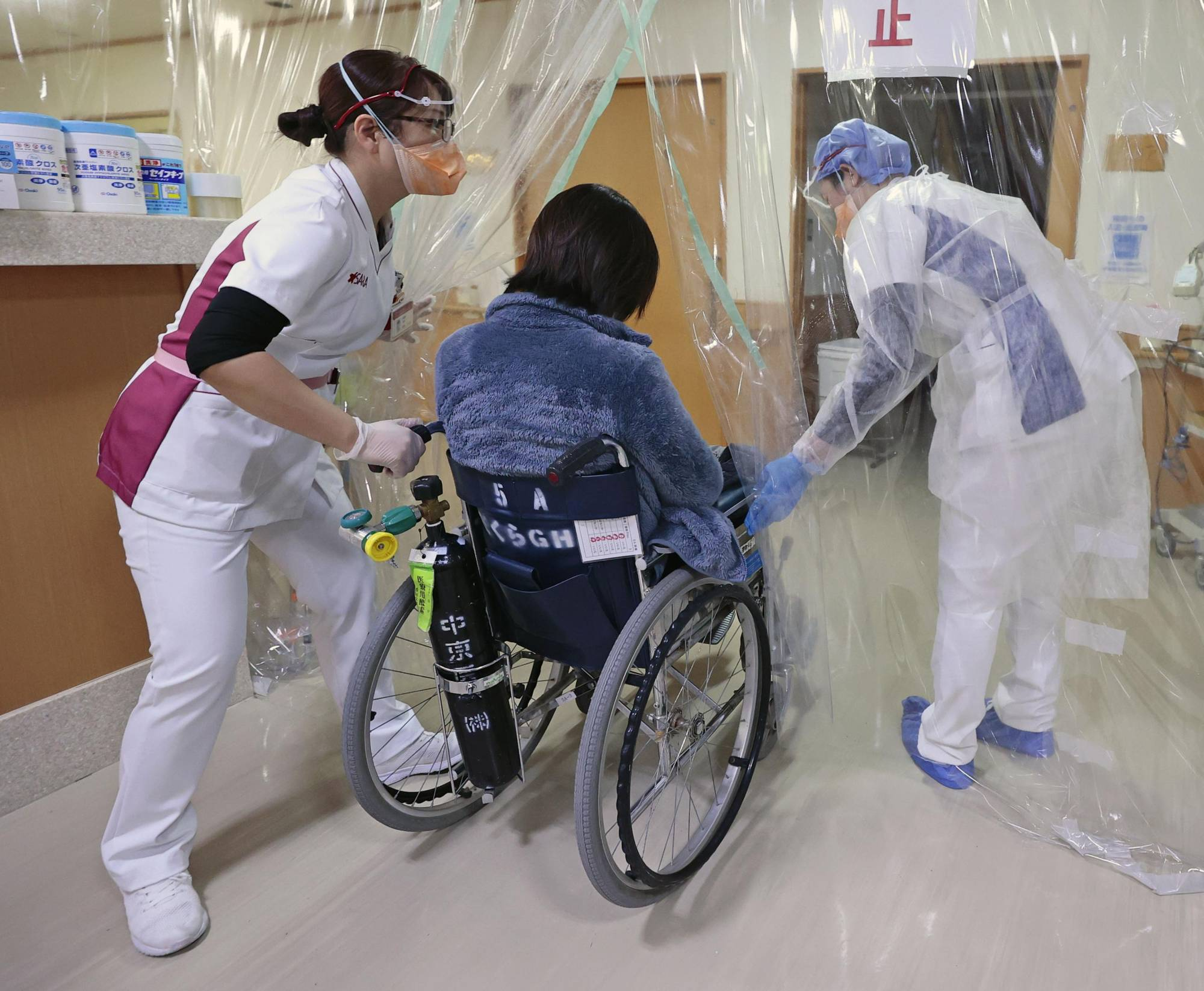 A coronavirus patient is wheeled inside Sakura General Hospital in the town of Oguchi, Aichi Prefecture, in January. A relative shortage of doctors is making it difficult for Japan to treat coronavirus patients. | KYODO