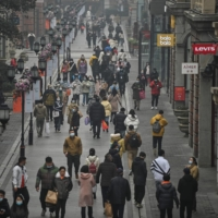 People walk along a pedestrian street in Wuhan, China, on Jan. 23, one year after the city went into lockdown to curb the spread of COVID-19.   AFP-JIJI