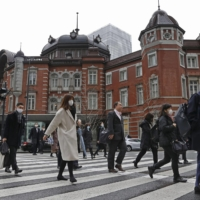 Commuters head to work in Tokyo's Marunouchi district on Tuesday morning, as the government was set to extend the state of emergency later in the day. | KYODO