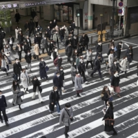 People come out from JR Osaka Station on Tuesday morning, as the government was set to extend the state of emergency later in the day.   KYODO