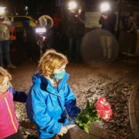 Children leave flowers at the entrance of The Coach House, the residence of Capt. Tom Moore, in Marston Moretaine, England, on Tuesday.  | REUTERS
