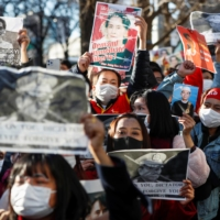 Myanmar people residing in Japan hold portraits of civilian leader Aung San Suu Kyi and Myanmar's President Win Myint at a rally against Myanmar's military after it seized power from a democratically elected civilian government and arrested the duo, outside the Foreign Ministry in Tokyo on Wednesday. | REUTERS
