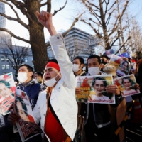 Myanmar people residing in Japan raise their fists outside the Foreign Ministry in Tokyo on Wednesday. | REUTERS