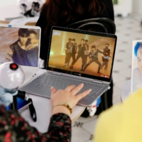 Fans of K-pop idol boy band BTS watch an online concert at a cafe in Seoul in October 2020. The diverse backgrounds of K-pop followers are seen as key to engaging fans in deeper discussions on a range of contemporary issues. | REUTERS