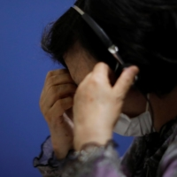 A volunteer responds to an incoming call at the Tokyo Befrienders call center, a Tokyo suicide hotline, in May. | REUTERS