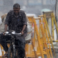 A commuter rides past during heavy rains in Chennai on Jan. 6.  | AFP-JIJI