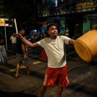 A man hits a plastic container to make noise after calls for protest went out on social media in Yangon, Myanmar, on Wednesday.  | AFP-JIJI