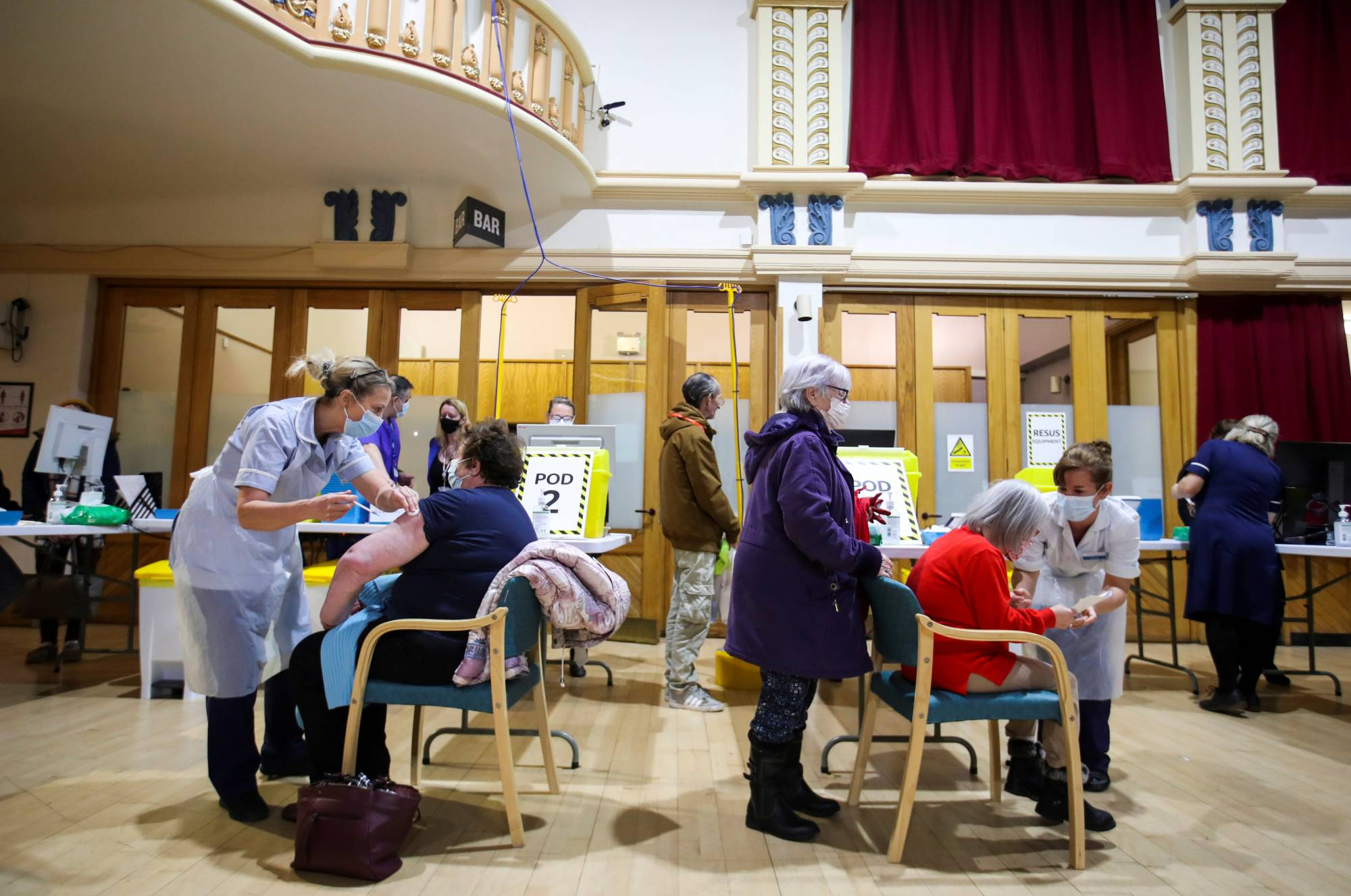 People receive COVID-19 vaccines in Chesterfield, England, on Wednesday. | REUTERS