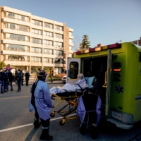 A woman is placed in an ambulance outside the Sienna St. George long term care home in Toronto, as frontline care workers hold a rally to demand better investment in resident care and staff safety. | REUTERS