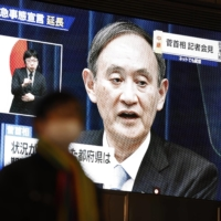 A TV shows Prime Minister Yoshihide Suga announcing an extension of the coronavirus state of emergency for Tokyo, Osaka and other regions by one month to March 7. | KYODO