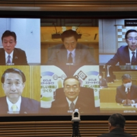 National Governors' Association members, in a meeting with economic revitalization minister Yasutoshi Nishimura (upper left) demand an early revision of the special measures law, on Jan.12. | KYODO