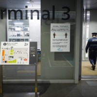 Police officers enter Narita Airport's Terminal 3. Travelers who break quarantine rules may face legal consequences such as having their names disclosed publicly or, in the case of foreign nationals, having their residency status revoked. | BLOOMBERG
