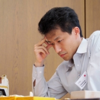 Tomohide Kawasaki studies the board during the European Shogi Championship in Germany in 2011. Kawasaki's YouTube channel helped introduce the rules and basic strategies of shogi to many foreign nationals.  | MISAKO IIJIMA-ROVEKAMP / VIA TOMOHIDE KAWASAKI