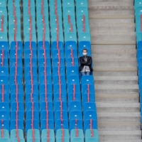 Red ribbons are placed on seats to maintain social distancing as a man sits alone ahead of a soccer match in Leipzig, Germany, in October.  | AFP-JIJI