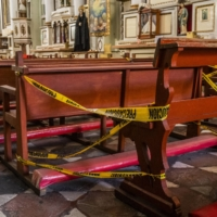 Pews are blocked off with caution tape for social distancing at a church in Puebla, Mexico, on Tuesday.  | BLOOMBERG