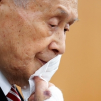 Tokyo 2020 Olympics chief Yoshiro Mori takes off his face mask during a news conference in Tokyo on Thursday. | POOL / VIA REUTERS