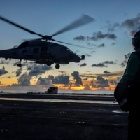 An MH-60R Sea Hawk helicopter launches during flight operations aboard the U.S. Navy aircraft carrier USS Ronald Reagan in the South China Sea in July 2020. | U.S. NAVY / VIA REUTERS
