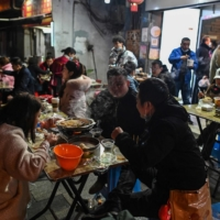 People eat in front of a restaurant in Wuhan, China, on Friday.  | AFP-JIJI