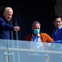 Peter Daszak (left) and Hung Nguyen-Viet (right), members of the World Health Organization team tasked with investigating the origins of COVID-19, stand on the balcony of their hotel in Wuhan, China, on Saturday.  | REUTERS