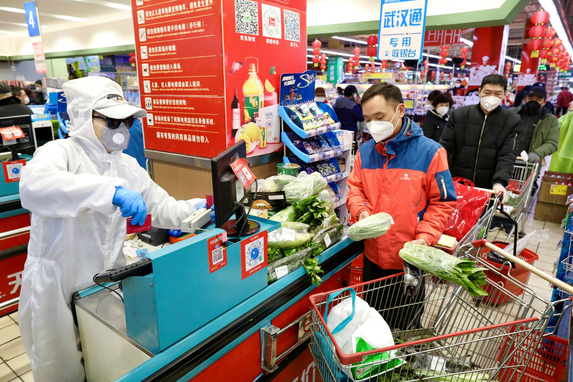 A worker in protective suit serves customers at a supermarket following the outbreak of the novel coronavirus in Wuhan, China, in February last year. | CHINA DAILY / VIA REUTERS