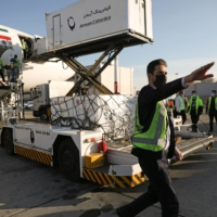 Cargo personnel work as the first shipment of Russia's Sputnik V vaccine arrives at Imam Khomeini Airport in Tehran on Thursday.  | WEST ASIA NEWS AGENCY / VIA REUTERS