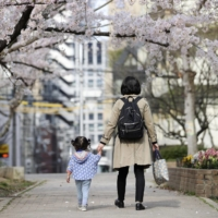 A mother and her child walk to nursery school in Osaka. | KYODO