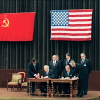 Then-U.S. Secretary of State George Shultz (left) and his Soviet counterpart, Eduard Shevardnadze, attend a signing ceremony with U.S. President Ronald Reagan and Soviet Communist Party General-Secretary Mikhail Gorbachev at the end of the two-day summit between the two superpowers in November 1985. | AFP-JIJI
