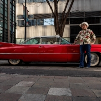 Hiroyuki Wada, who runs a vintage car service company, poses for with a 1959 Cadillac Coupe DeVille on Jan. 16. | AFP-JIJI