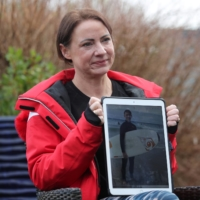Sally Flavill shows a photograph of her nephew, Joseph Flavill, in Nottingham, England, on Friday. Joseph, 19, is slowly emerging from a coma, but has no knowledge of the coronavirus pandemic, which erupted after he was injured in a car accident in March last year. | REUTERS