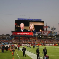 President Joe Biden and first lady Jill Biden are seen delivering a message on the big screen before Super Bowl LV in Tampa, Florida, on Sunday. | REUTERS