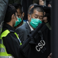 Media tycoon Jimmy Lai (right) is escorted into a prison van outside the Court of Final Appeal in Hong Kong on Feb. 1, after being ordered to remain in jail while judges consider his fresh bail application. | AFP-JIJI