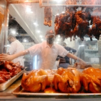 An employee reaches for roasted meat in the display window at a Hong Kong-style barbecue restaurant in Richmond, British Columbia.    REUTERS
