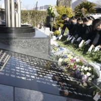 Students of Uwajima Fisheries High School in Ehime Prefecture offer flowers on Wednesday at a monument to victims of a fatal collision between the school's training boat Ehime Maru and a U.S. nuclear submarine off Hawaii in 2001. | KYODO