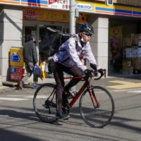 On the go: A helmeted cyclist passes in front of a convenience store in the Tokyo metropolitan area. | PHOEBE AMOROSO