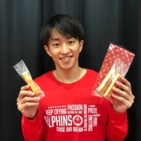 Nagoya guard Takumi Saito holds snacks in packaging created with biomass materials. | COURTESY OF THE NAGOYA DIAMOND DOLPHINS